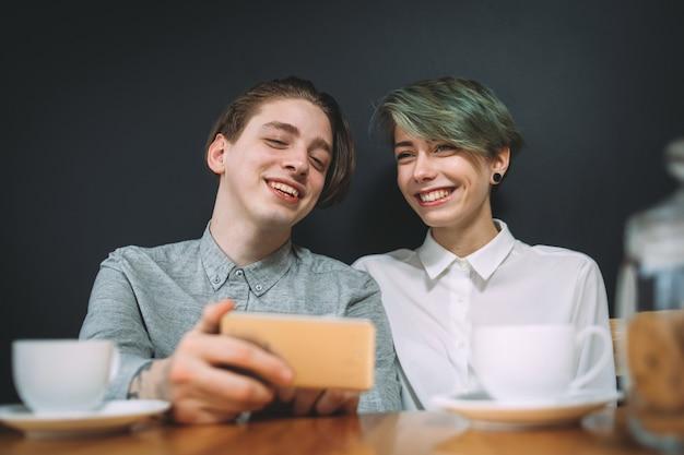 Concept de communication amitié bff. meilleurs amis assis dans un café en train de rire de photos ou de vidéos amusantes sur smartphone