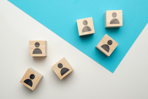 Concept de compétition d'équipe au travail avec des icônes sur des blocs de bois.