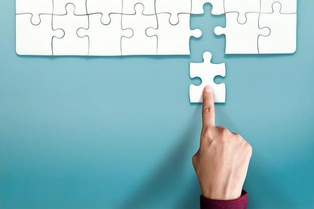 Concept complet. main remplacer une pièce finale de puzzle dans un dernier blanc