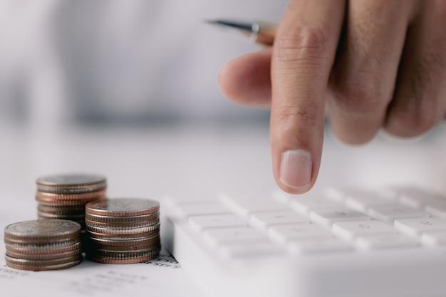 Concept de comptabilité la calculatrice de poussée de main masculine est allongée sur le bureau dans le cadre du bureau à domicile