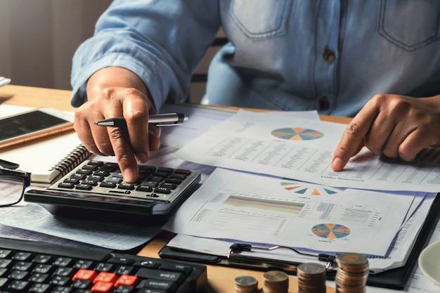 Concept comptable. femme affaires, fonctionnement, utilisation, calculatrice, à, pile argent, dans, bureau