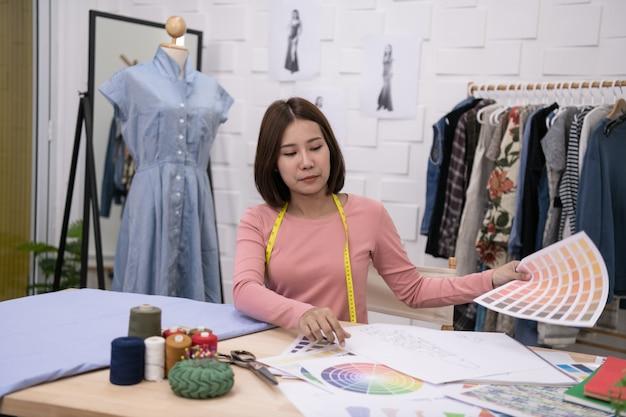 Concept de concepteur. la couturière conçoit une robe de soirée dans la chambre