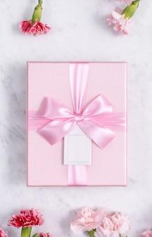 Concept de conception de cadeau de voeux de vacances de fête des mères avec bouquet d'oeillets sur fond de marbre blanc