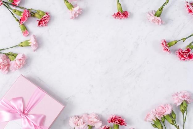 Concept de conception de cadeau de voeux de vacances fête des mères avec bouquet d'oeillets sur fond de marbre blanc