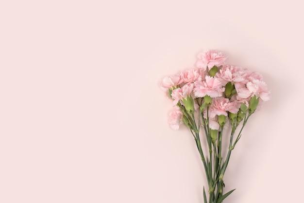 Concept de conception de la conception de voeux de vacances de fête des mères avec bouquet d'oeillets sur fond de table rose pastel