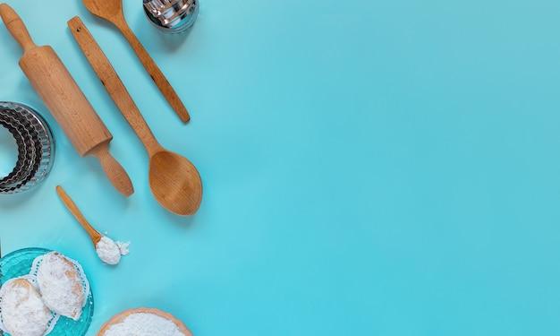 Concept de conception de fabrication de biscuits traditionnels de chypre, de cuillères en bois de cuisson, de rouleau à pâtisserie, de moules en métal, de poudre de sucre, vue de dessus de mise en page, mise à plat, frais généraux, espace de copie vierge sur fond bleu