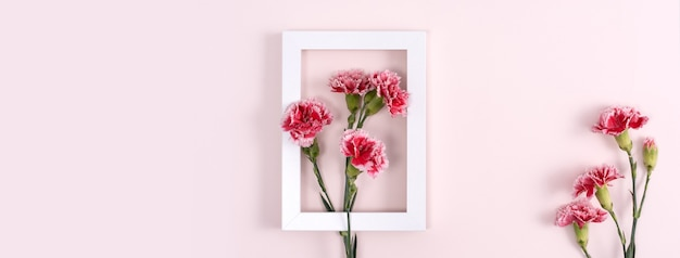Concept de conception de fond de voeux de vacances fête des mères avec bouquet d'œillets sur fond rose