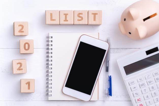 Concept de conception de liste financière 2021 avec cahier vierge, tirelire, calculatrice et bloc de bois.