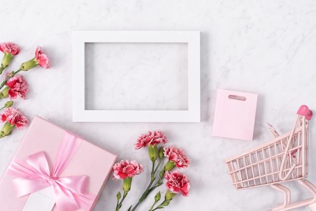 Concept de conception de voeux de vacances fête des mères avec bouquet d'oeillets et cadeau sur fond de marbre blanc
