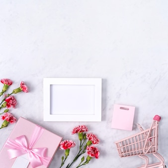 Concept de conception de voeux de vacances fête des mères avec bouquet d'oeillets et cadeau sur une surface en marbre blanc