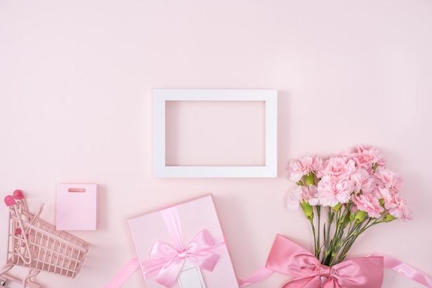Concept de conception de voeux de vacances de fête des mères avec bouquet d'oeillets et cadeau sur la surface rose