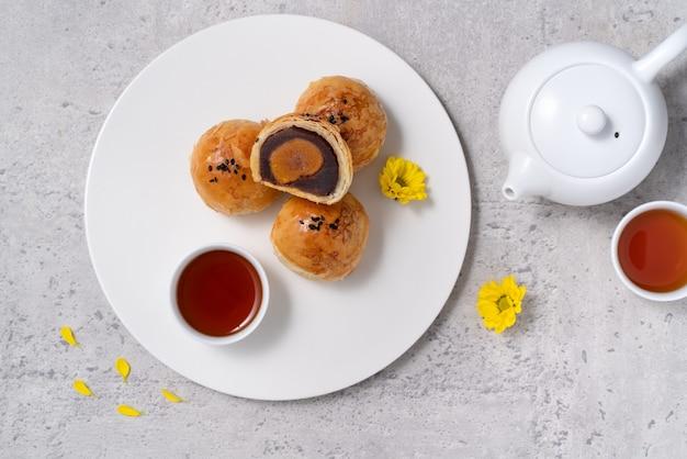 Concept de conception vue de dessus de la pâtisserie jaune de gâteau de lune, gâteau de lune pour les vacances de la fête de la mi-automne sur fond de table gris foncé
