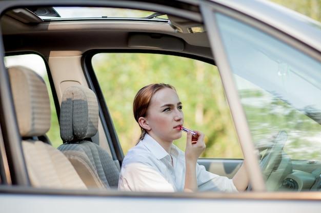 Concept de conduite dangereuse. jeune femme pilote adolescente aux cheveux rouges peindre ses lèvres faisant l'application de maquillage tout en conduisant la voiture