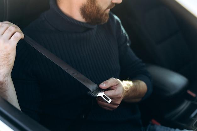 Concept de conduite sûre. jeune homme positif attachant la ceinture de sécurité de la voiture, vue latérale, espace de copie. gai gars caucasien commençant un voyage en voiture, louant une belle auto confortable pour voyager