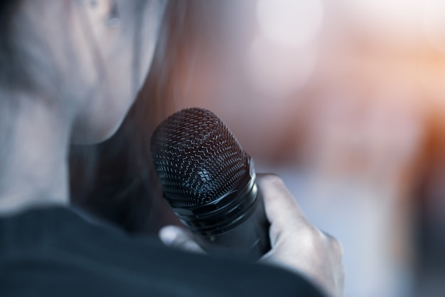 Concept de conférence: verso du discours d'une femme d'affaires intelligente et avec un microphone