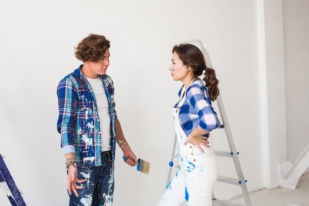 Concept de conflit, de réparation, de rénovation et de personnes - un couple faisant une réparation dans un appartement et se disputent