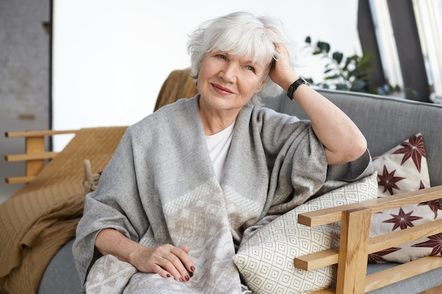 Concept de confort, design d'intérieur, loisirs, mode de vie et personnes âgées. attractive élégante femme mûre retraité avec des rides et des cheveux gris reposant sur un canapé dans sa maison de campagne, souriant