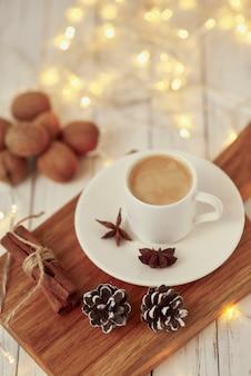 Concept confortable d'automne ou d'hiver. tasse de café avec guirlandes lumineuses et décoration /