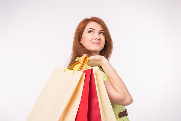 Concept de consommateur, de vente et de personnes - style femme rousse tenant des sacs à provisions