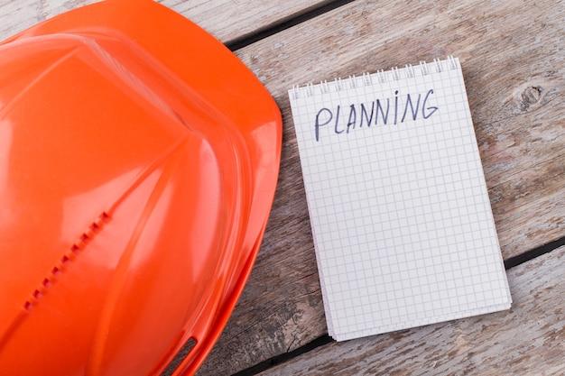 Concept de construction de constructeur de planification. casque de travailleur et bloc-notes sur table en bois vieilli.