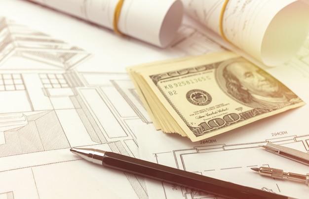 Concept de construction et de structure. blueprints pour le projet architectural, la construction et l'ingénierie. bureau de bureau avec de l'argent et un stylo