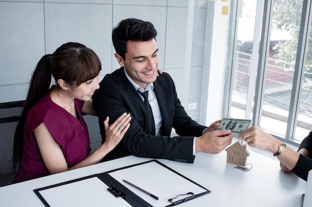 Concept de contrat d'achat ou de location d'une maison. le couple mari et femme paient pour acheter une maison avec l'entrepreneur. les entrepreneurs reçoivent un paiement des clients lors de la vente de maisons.