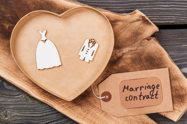 Concept de contrat de mariage. boîte en bois en forme de coeur avec des vêtements de mariée et de marié.