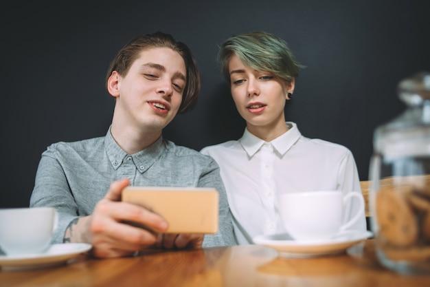 Concept de convivialité amitié bff. meilleurs amis assis dans un café en train de regarder des photos ou de regarder des vidéos sur un smartphone