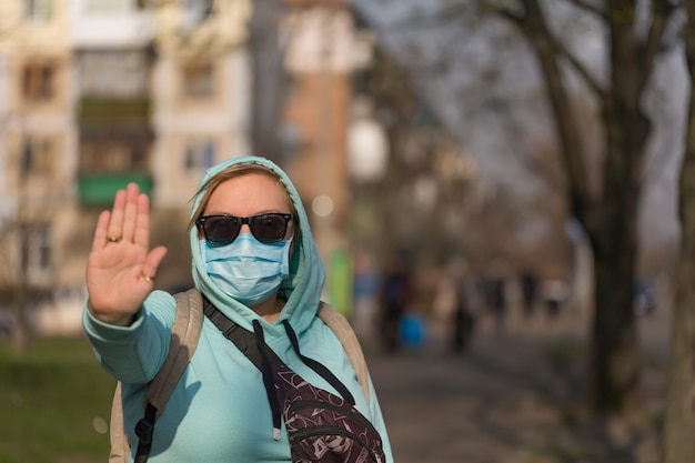 Concept de coronavirus appel mondial à rester à la maison. fille portant un masque de protection contre la maladie et montrant un geste d'arrêt des mains pour arrêter l'épidémie de coronavirus.