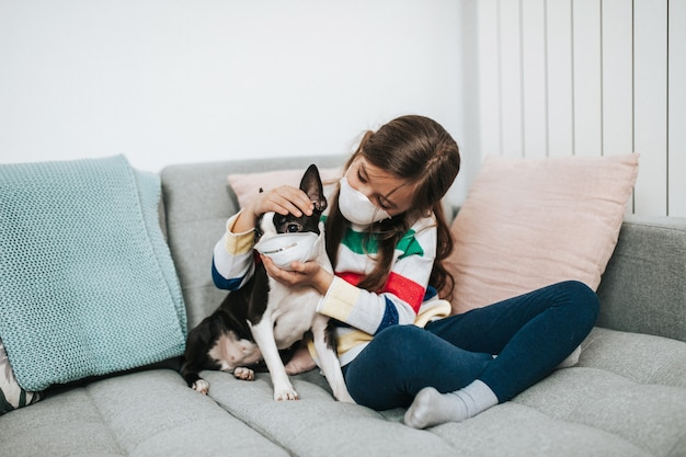 Concept de coronavirus covid-19. une fille et son chien avec des masques de protection sur le visage jouent à vivre pendant qu'ils sont en quarantaine.