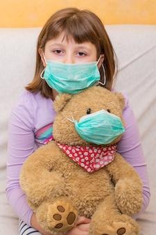 Concept de coronavirus: jeune fille énorme un ours en peluche avec masque médical