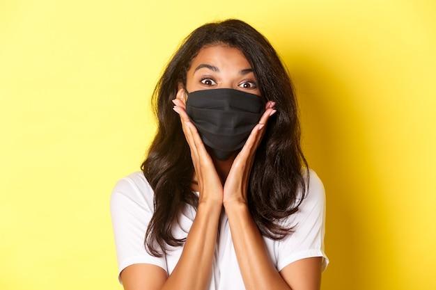 Concept de coronavirus, pandémie et mode de vie. gros plan d'une fille afro-américaine émerveillée en masque noir, se demandant quelque chose de génial, fond jaune.