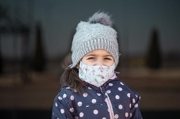 Concept de coronavirus .une petite fille porte un masque sur son visage lors d'une épidémie de virus