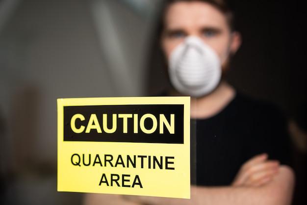 Concept de coronavirus, de quarantaine et de pandémie. homme triste et malade du virus corona regardant par la fenêtre