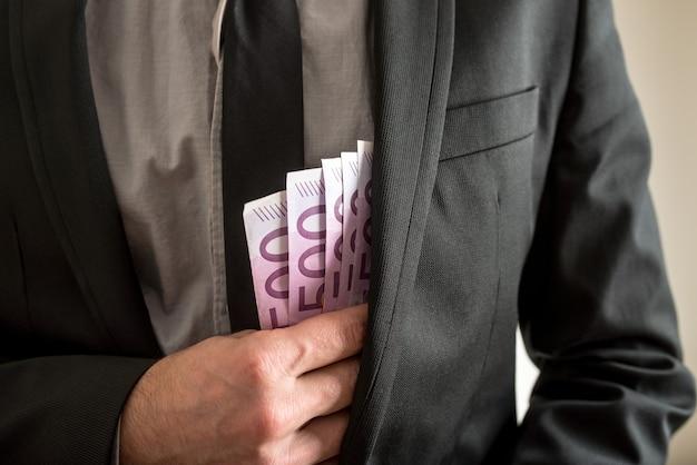 Concept de corruption - gros plan d'homme d'affaires mettant cinq cents billets en euros dans la poche intérieure de sa veste de costume.