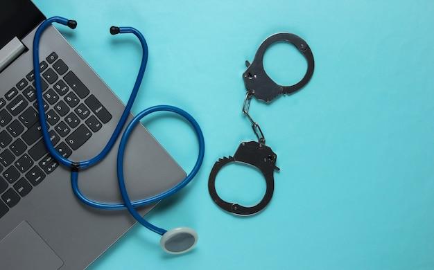 Concept de corruption en médecine. ordinateur portable avec un stéthoscope et des menottes sur fond bleu. nature morte médicale. punition pour crime