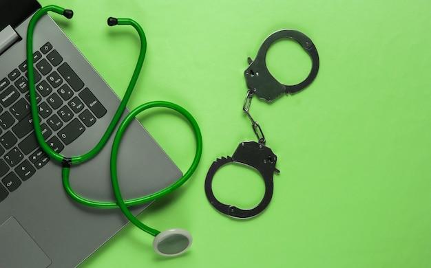 Le concept de corruption en médecine. ordinateur portable avec un stéthoscope et des menottes.. nature morte médicale. punition pour crime