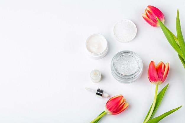 Concept de cosmétiques faits maison bio naturels. soins de la peau, remèdes et produits de beauté: contenants de crème et de sérum parmi les fleurs de tulipes rouges de printemps sur fond blanc