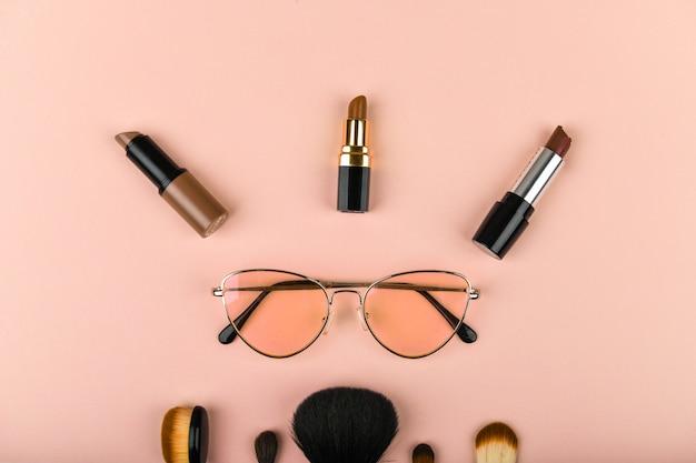 Le concept de cosmétiques féminins. moyens improvisés féminins. ensemble de cosmétiques colorés sur un rose. mise à plat.