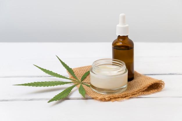Concept de cosmétiques infusés de cannabis crème cbd et huile de chanvre sur fond blanc avec espace de copie
