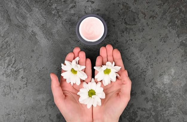 Le concept de cosmétiques naturels. fleurs et un pot de crème. camomille en forme de coeur et un pot de crème. vue d'en-haut. cosmétique naturel. lieu d'enregistrement.