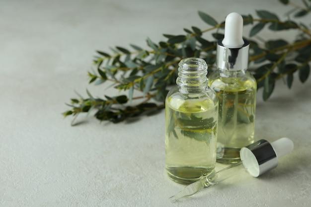 Concept de cosmétiques naturels à l'huile d'eucalyptus sur table texturée blanche