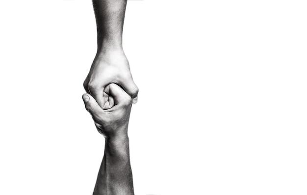 Concept de coup de main et journée internationale de la paix, soutien. main tendue, bras isolé, salut. gros plan sur la main d'aide. deux mains, bras aidant d'un ami, travail d'équipe. noir et blanc.