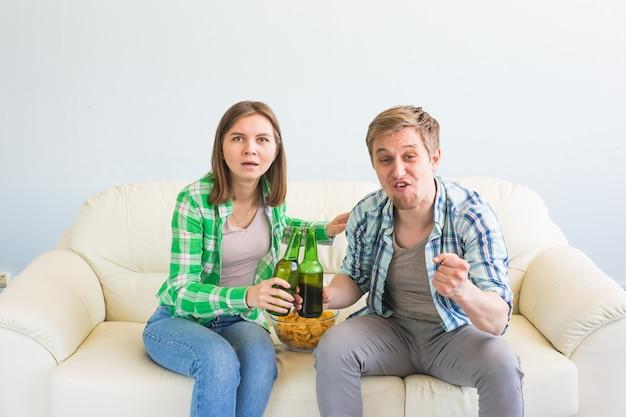 Concept de coupe du monde de football - couple moderne à la recherche d'un jeu de sport excité et heureux à la télévision