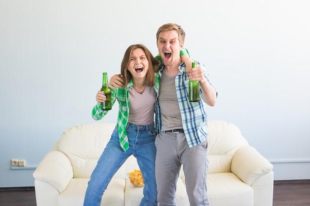 Concept de coupe du monde de football - de jeunes amis boivent de la bière et acclament le football