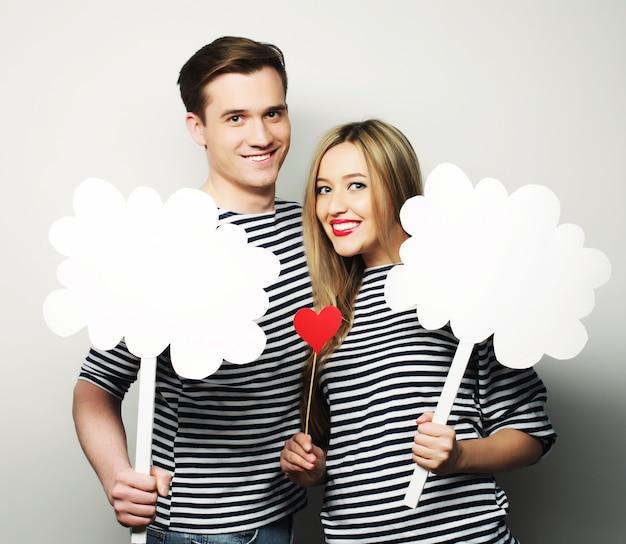 Concept de couple, d'amour et de famille: couple amoureux tenant du papier blanc sur bâton.