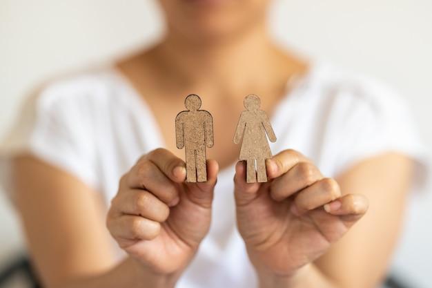 Concept de couple et de famille. gros plan de la main de femme tenant l'icône homme et femme en bois.