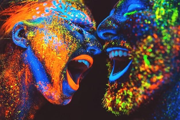 Concept. couple souriant. portrait d'une paire d'amants peints en poudre fluorescente.