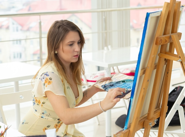 Concept de cours d'art, de dessin et de créativité - étudiante assise devant un chevalet avec palette et pinceau.