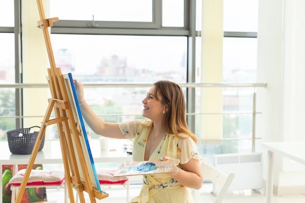 Concept de cours d'art, de dessin et de créativité - étudiante assise devant un chevalet avec palette et pinceau